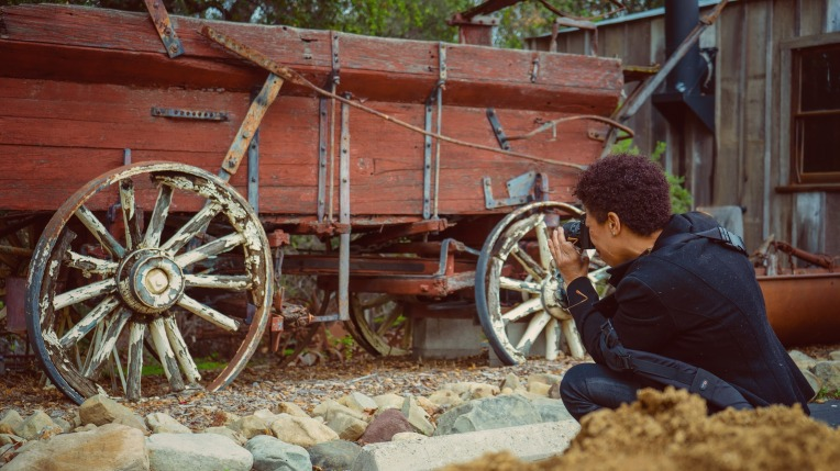 A photographers taking pictures of a wagon wheel at stagecoach inn in Newbury Park ca