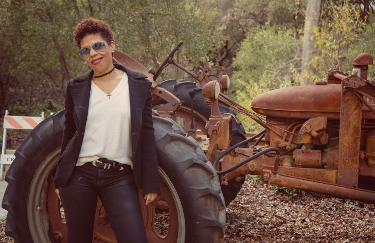 Model standing in front of a vintage tractor wearing raybans