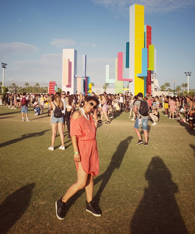 Girl in an orange dress and black sneakers in front of art installation at Coachella festival