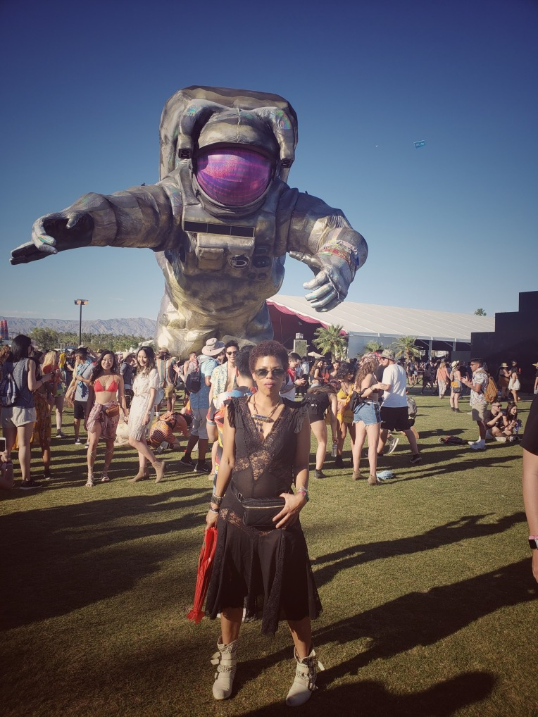 Woman in black dress in front of the Coachella spaceman