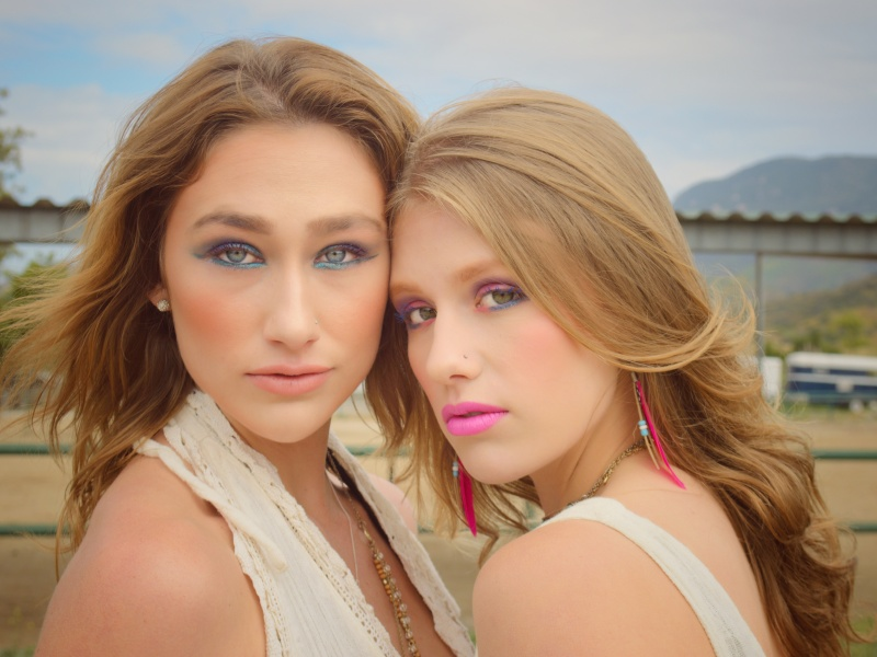 Two young women with 80's style makeup posing face to face on a horse ranch