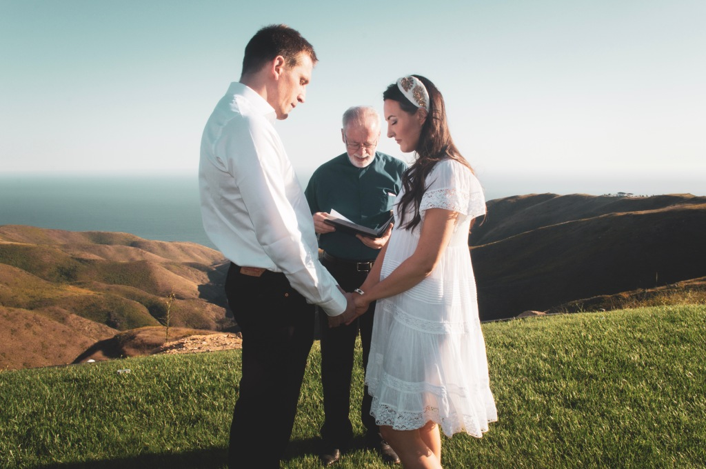 Couple getting married on a mountain side overlooking the ocean