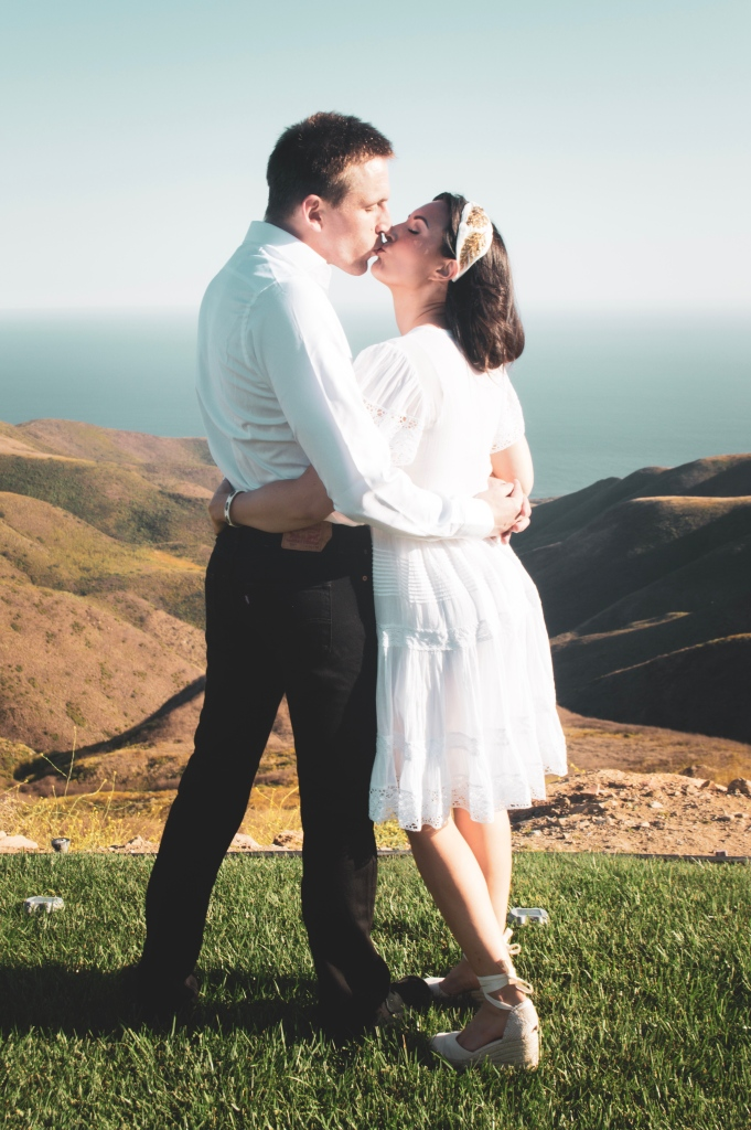 Bride and groom kissing on a mountainside overlooking the ocean