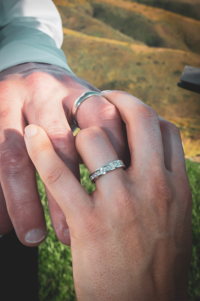 Fingers intertwined with wedding bands