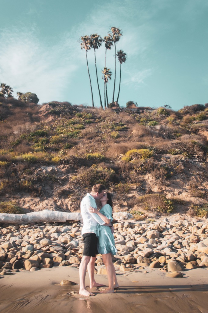 Couple kissing on the beach with palm trees