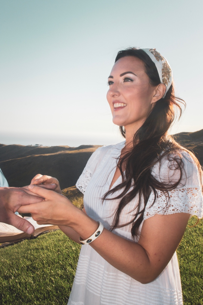 Bride smiling while placing wedding band on finger