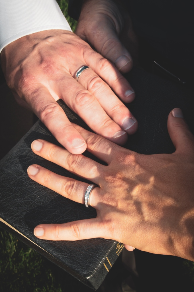 Hands with wedding rings placed on a bible
