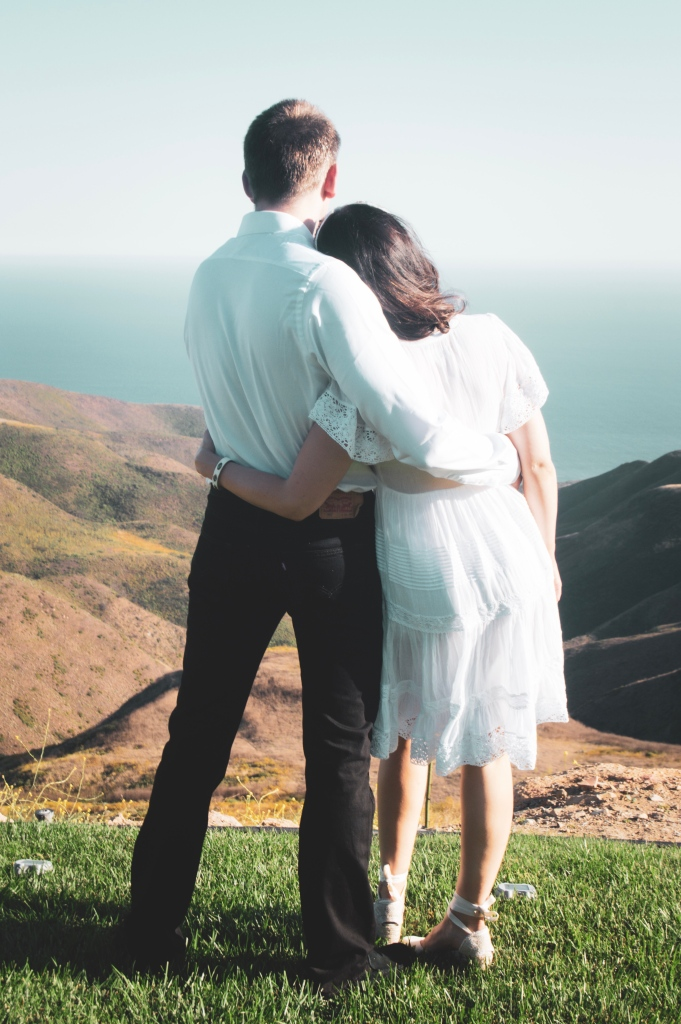 Bride and groom standing side by side hugging looking at the ocean