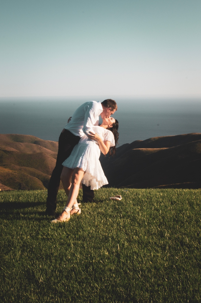 Man dipping a woman for a kiss on a mountainside overlooking the ocean