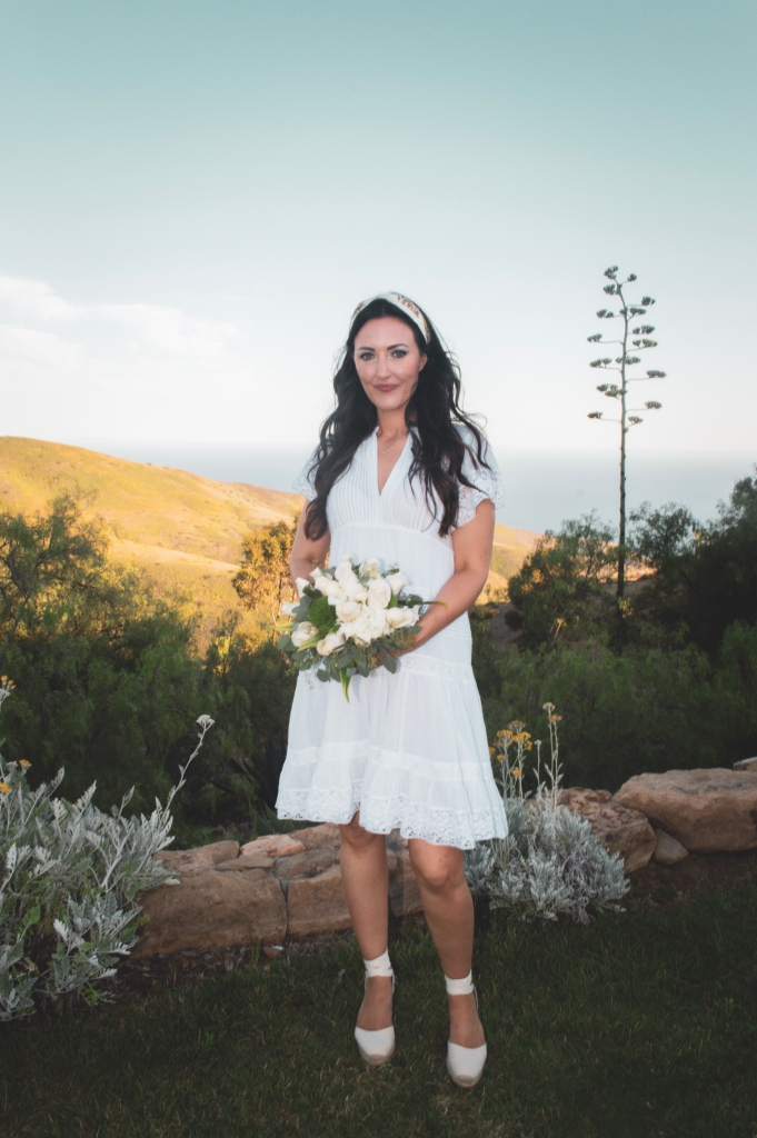 Bride holding white rose bouquet on a mountainside with the ocean view