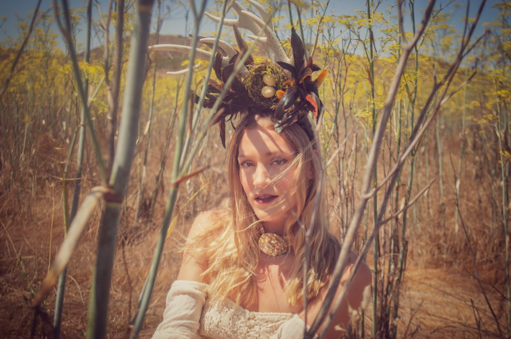 Woman in a mustard field wearing a horn head piece