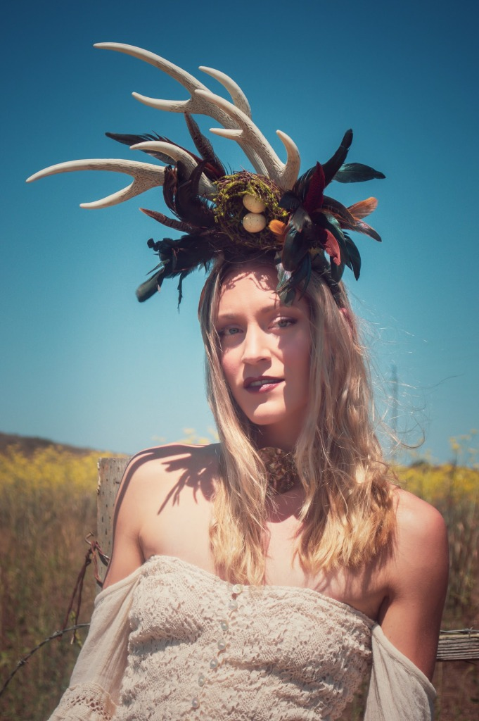 Woman with blue sky wearing a decorative horn head piece