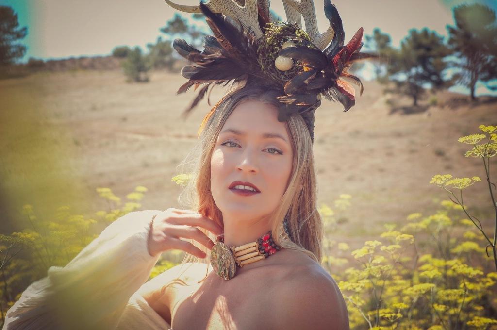 Woman in a mustard field wearing a horn head piece
