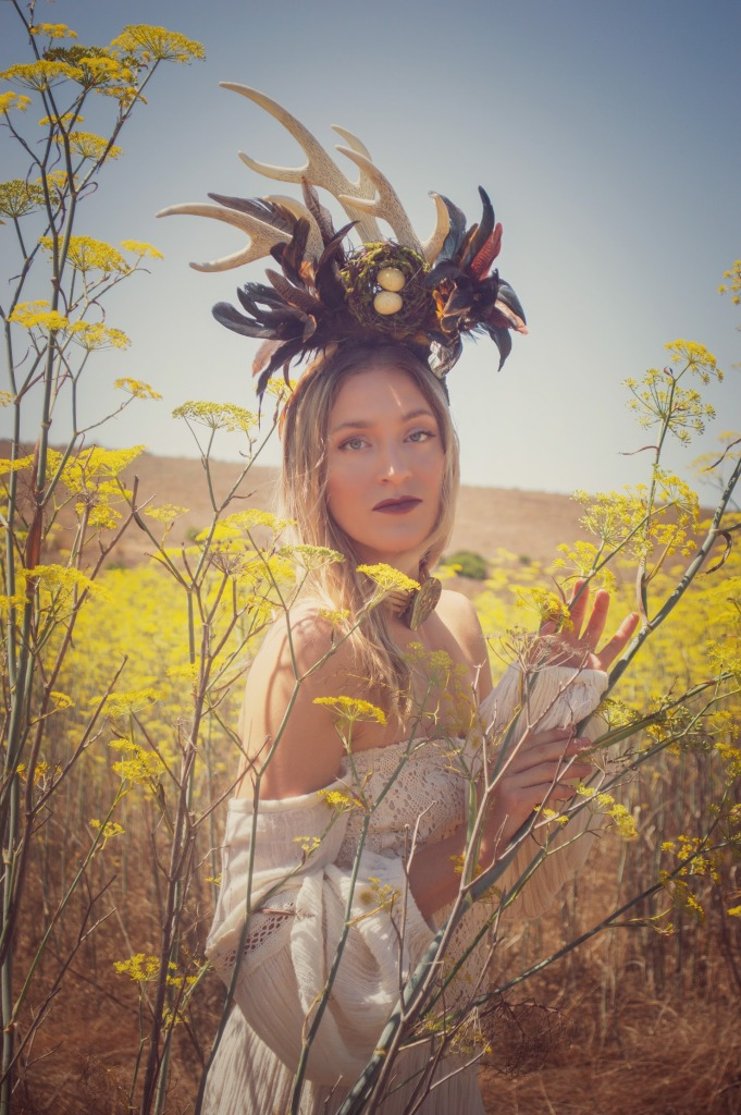 Blonde Woman standing in a mustard field in a white dress wearing a horn head piece
