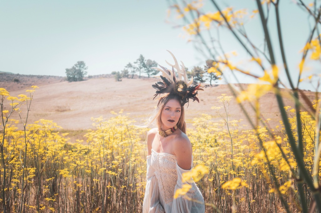 Woman standing in a mustard field in a white dress wearing a horn head piece