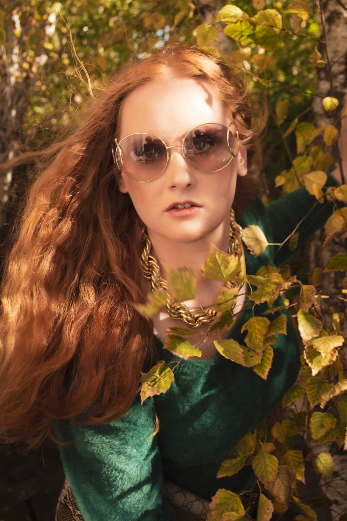 Portrait of a redhead in surrounded by fall leaves wearing sunglasses