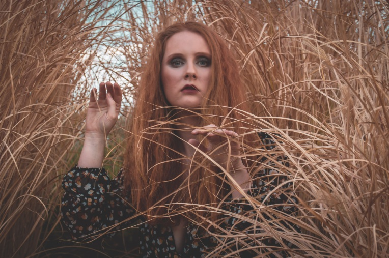 redhead woman standing in pampas grass