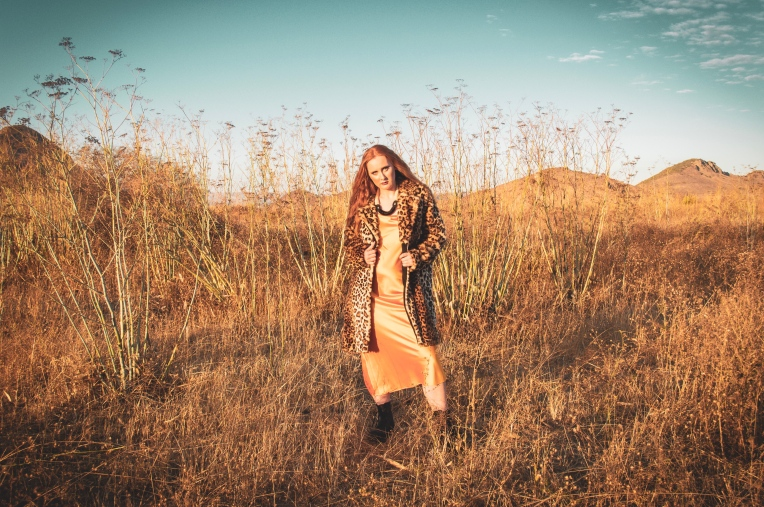 redhead standing in a field wearing a yellow dress and a leopard coat
