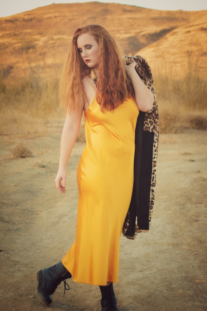 redhead in a field wearing a yellow dress