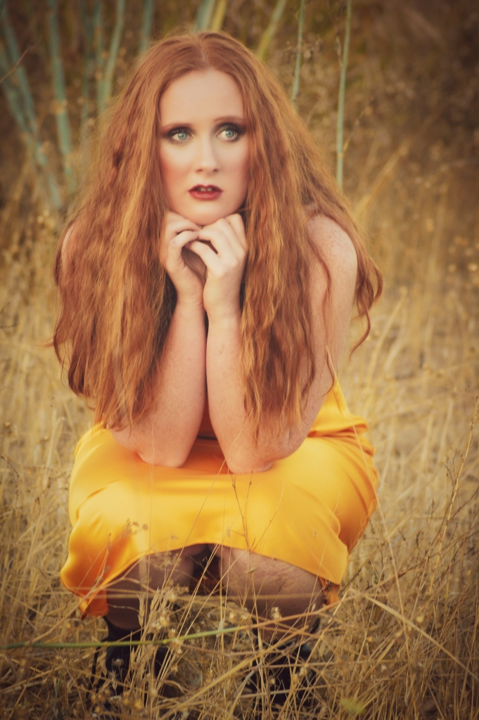 redhead squatting in a field wearing a yellow dress