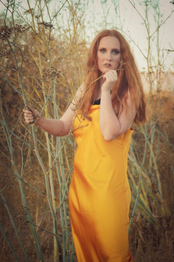 redhead standing in tall grass wearing a yellow dress