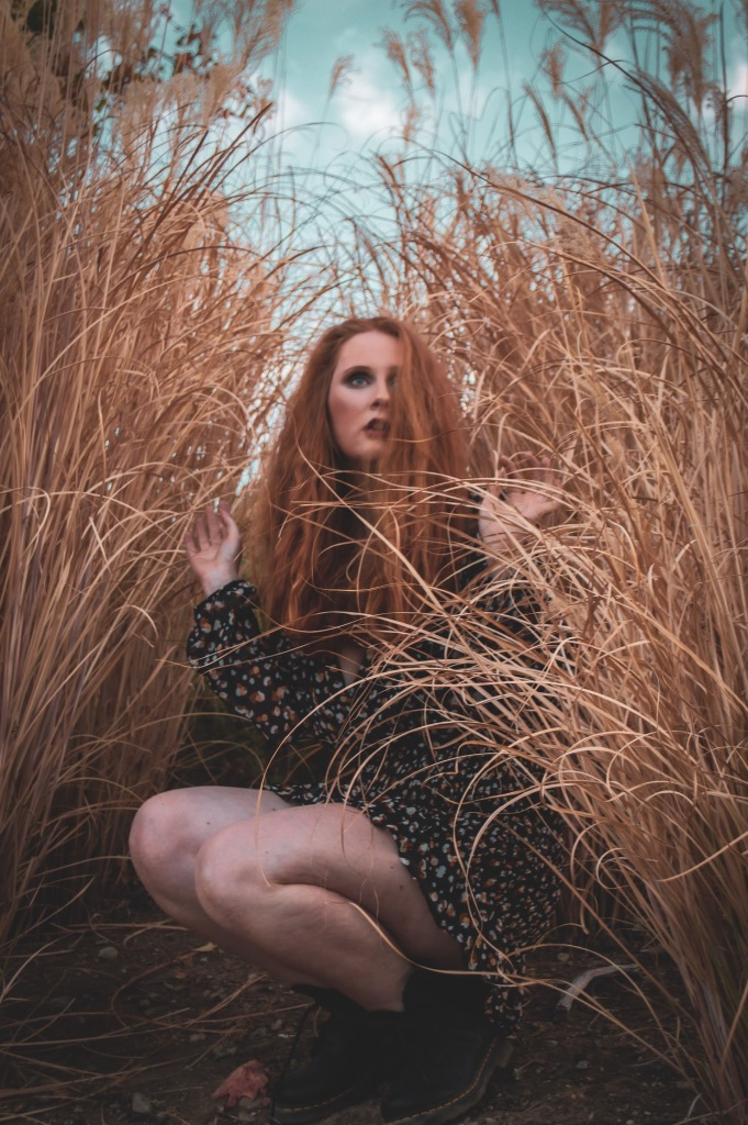 redhead woman squatting surrounded by pampas grass in a floral dress