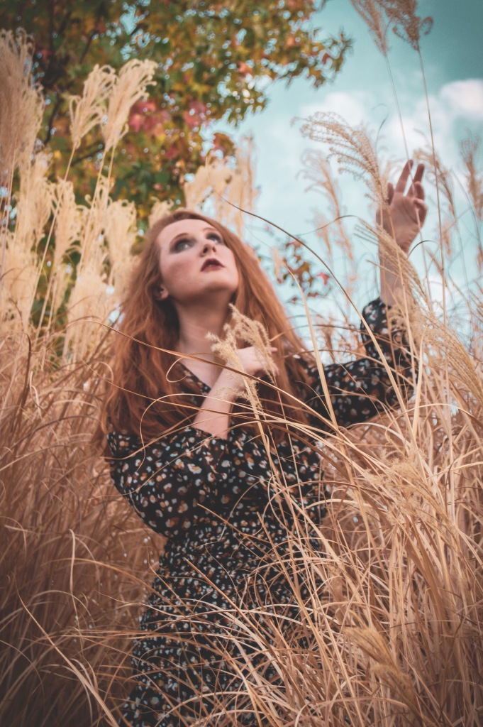 redhead Girl standing in pampas grass looking up into the sky